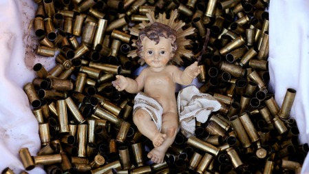 A statue of the baby Jesus on a bed of bullet shells is seen in a Nativity scene outside the Basilica of St Francis in Assisi